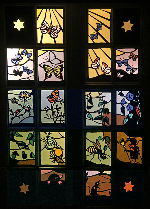In dem beleuchteten Fenster lassen sich viele Schmetterlinge finden.