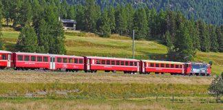 Zug der Rhätischen Bahn fährt durch eine Landschaft im Engadin