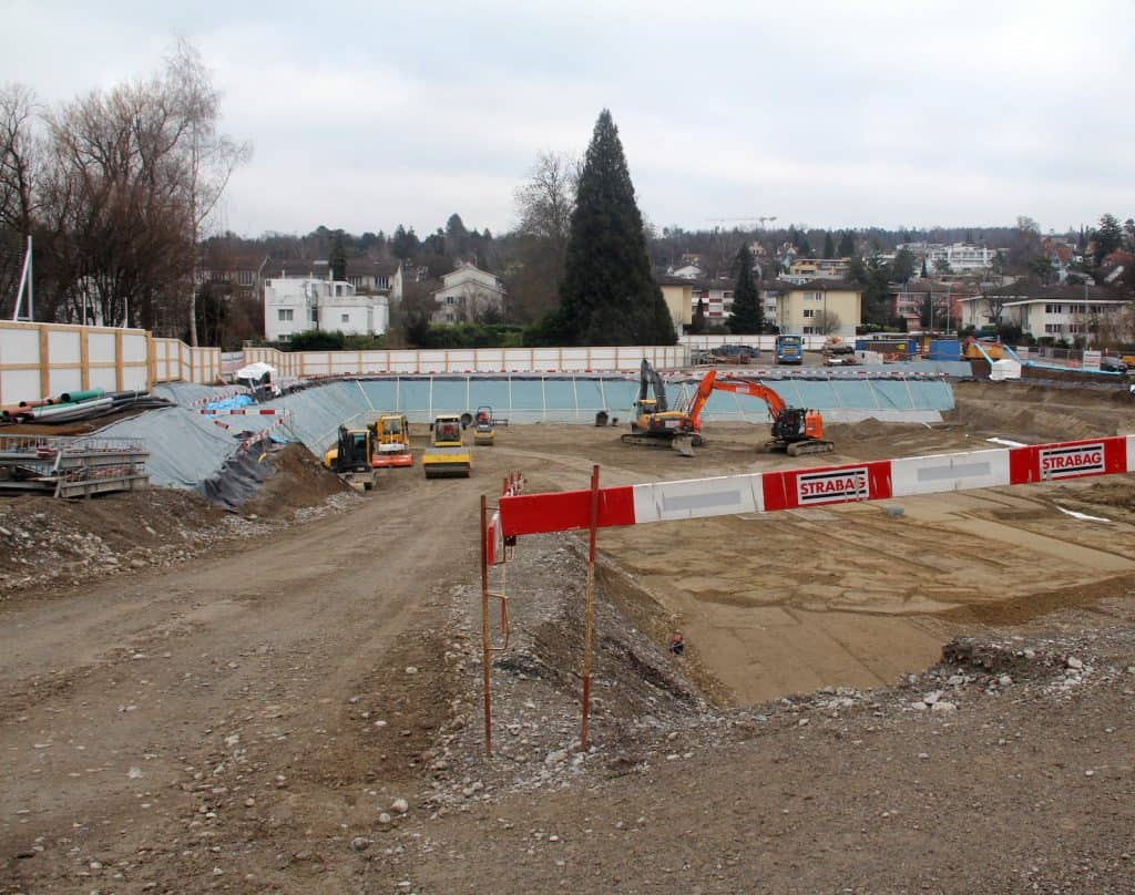 Wiese und Schrebergärten weichen einer Baustelle.
