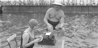 Altes Schwarz-Weiss Foto: Sekretärin mit Schreibmaschine und Chef sitzen im Wasser, um der Hitze zu entgehen.