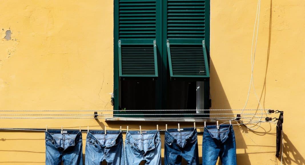 Jeans hängen an einer Wäscheleine vor einer Hauswand. Viele Chemikalien werden zur Herstellung von Jeans benötigt.