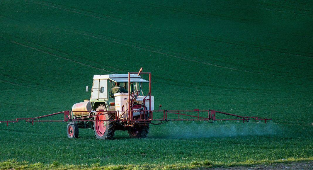 Ein Traktor fährt über den Acker und spritzt Pestizide.