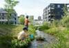 Naturnahe Siedlungsumgebung mit Bach und spielenden Kindern.