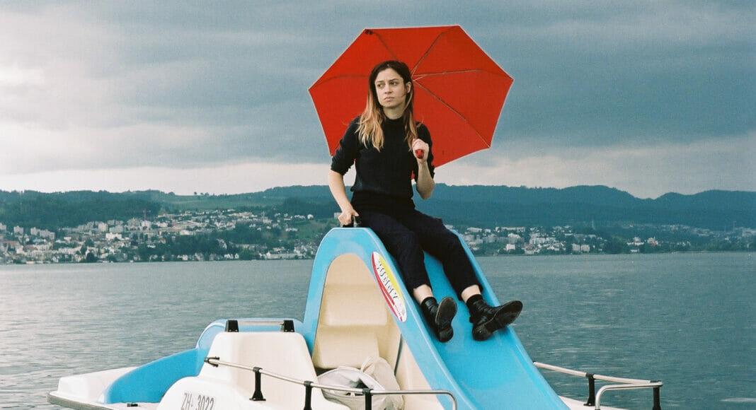 Lara Stoll mit Regenschirm auf einem Pedalo