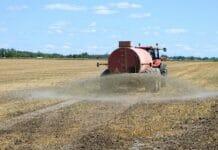 Traktor auf Feld beim Ausbringen von Gülle