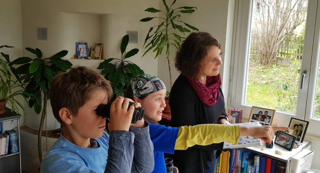 Familie beobachtet Vögel vom Wohnzimmer aus
