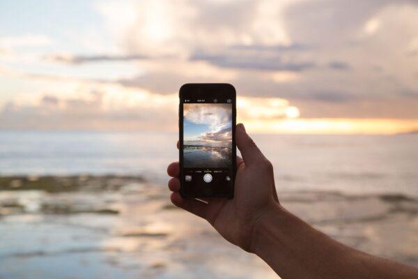Hand hält Handy, im Hintergrund Wasser