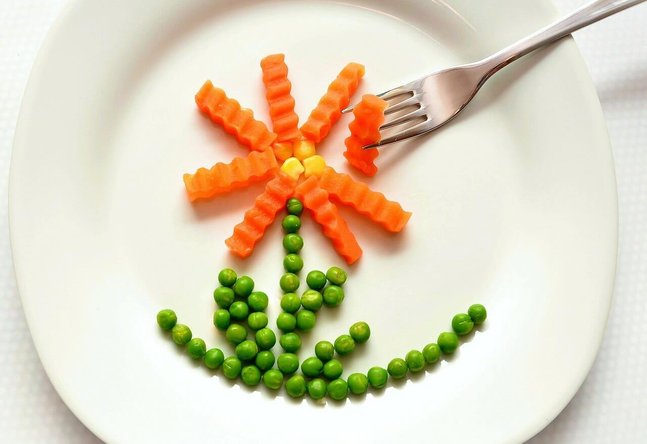 Teller mit Erbsen und Karotten.