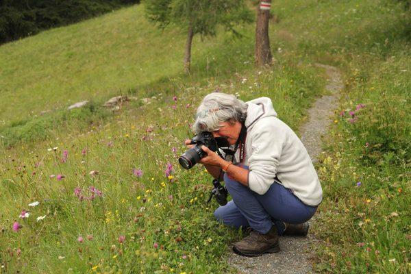 Christine Dobler Gross macht ein Foto in der Blumenwiese.